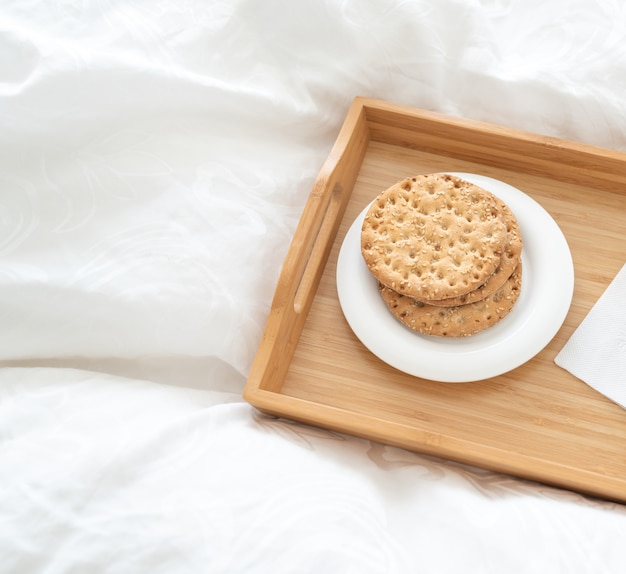 Tray with water and crackers dbreakfast on a bed