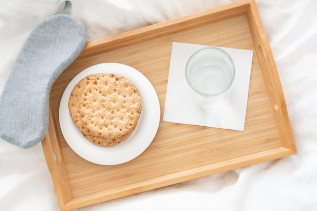 Tray with water and crackers dibreakfast on a bed