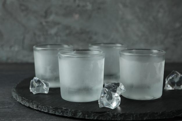 Поднос с мокрыми рюмками водки и льда на темном столе