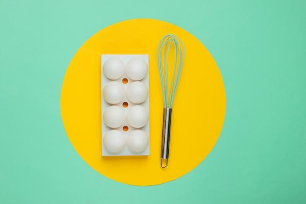 白い鶏の卵を入れたトレイに、真ん中に黄色い円が入った青を泡だて器で混ぜます。