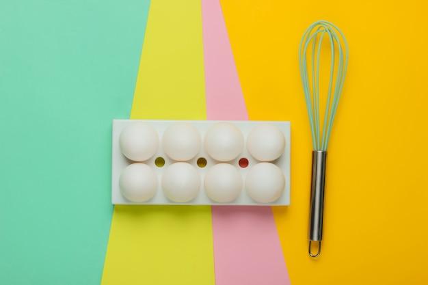 白い鶏の卵を入れたトレイと色付きの泡だて器