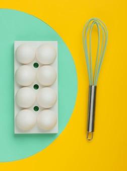 白い鶏の卵でトレイを作り、真ん中に青い円が付いた黄色で泡だて器で泡立てます。