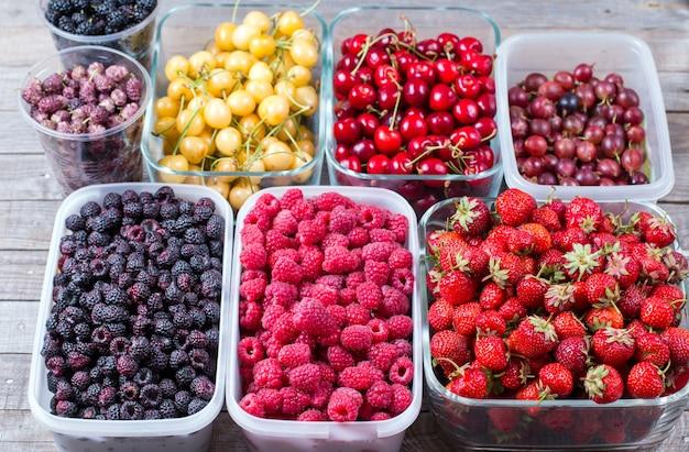 Подносы со свежими ягодами в пластиковых подносах на деревянном столе
