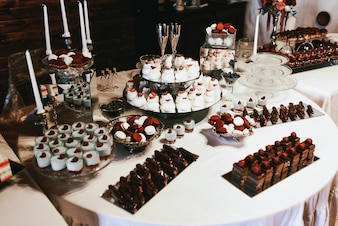 Trays with chocolate cakes and eclairs stand on white table