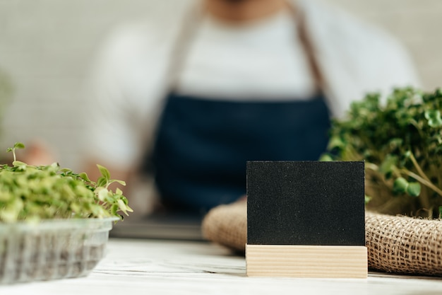 コピースペース付きの小さな黒い銘板が付いたテーブルにマイクログリーンのトレイ