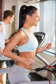 Тренировка на беговой дорожке. вид сбоку привлекательной молодой женщины, бегущей на беговой дорожке и улыбающейся с мужчиной, тренирующимся на заднем плане
