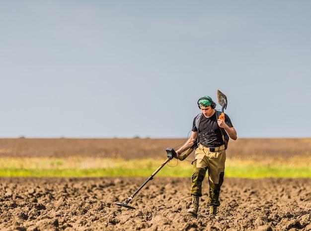 Охотник за сокровищами с металлоискателем в поле.