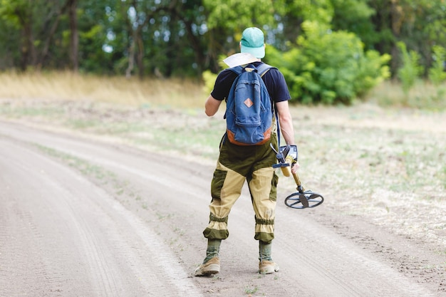 Treasure hunter with metal detector and shovel on the road