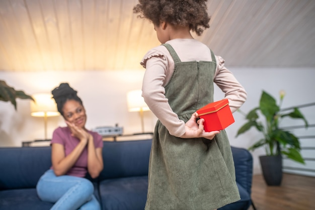 Treasured red box. little red box in hands behind back of little darkskinned girl standing in front of happy mother sitting on couch