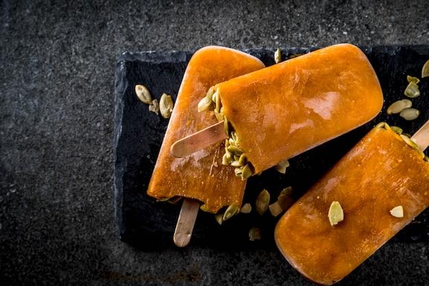 感謝祭、ハロウィーンの御treat走。黒い石のテーブルの上の種とカボチャのアイスクリームアイスキャンディー。