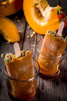 感謝祭、ハロウィーンの御treat走。かぼちゃのアイスクリームアイスキャンデーの種子、メープルシロップのグラス。木製の古い素朴なテーブル。