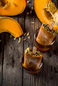 カボチャの秋の料理のアイデア。感謝祭、ハロウィーンの御treat走。かぼちゃのアイスクリームアイスキャンデーの種、メープルシロップのグラス。木製の古い素朴なテーブル。コピースペーストップビュー