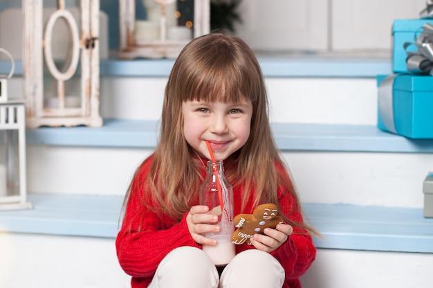 メリークリスマス!クリスマスイブにサンタを待っている、クッキーを食べて牛乳を飲むかわいい女の子。子供はサンタクロースの御treat走を準備します:ジンジャーブレッドマンとミルク。