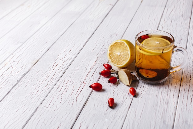 Лечить простуду. горячий чай с лимоном и ягодами стоит на белом деревянном столе