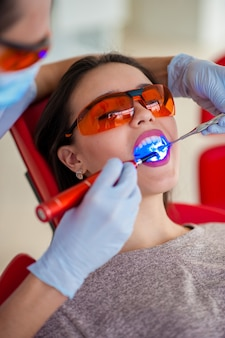 Treatment of light seal beautiful girl in dentistry.