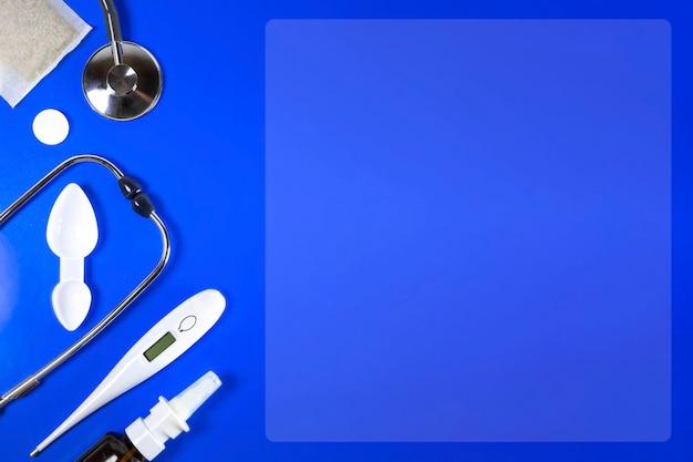 감기와 독감의 치료. 아픈 날과 의료 휴가 개념. 다양한 의약품, 온도계, 파란색 배경, 전통 의학, 독감 개념에 코가 막힌 스프레이. 공간을 복사합니다.
