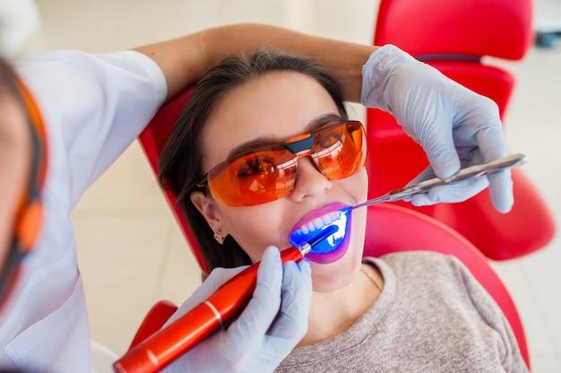 Лечение светлой печатью красивой девушки в стоматологии.