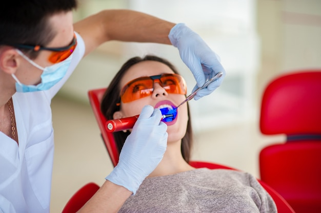 Лечение светлой печати красивой девушки в стоматологии.