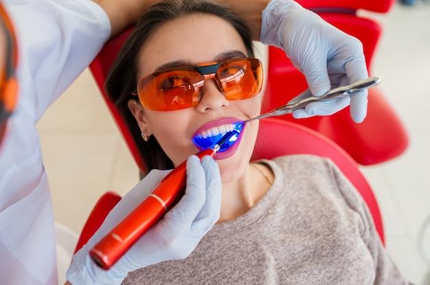 Лечение световой печати красивой женщины в стоматологии