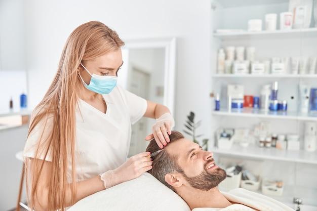 Лечение молодого человека косметологом для подтяжки и разглаживания морщин на коже лица. инъекции мезотерапии привлекательному мужчине.