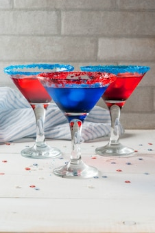 Treats for independence day holiday on july 4 homemade alcoholic cocktails punch in traditional colors - red blue white with ice on the home kitchen table