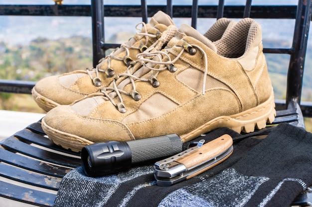 Trecking or hiking equipment - boots, socks, folding knife and flashlight. stock photo