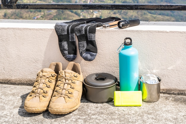 Trecking or hiking equipment - boots, socks, folding knife, gas burner, water flask, kettle pot and flashlight. outdoor activity concept. still life close up stock photo.