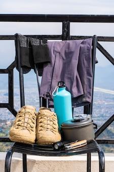 트레킹 또는 하이킹 장비 - 부츠, 양말, 바지, 접이식 칼, 물 플라스크, 주전자 냄비 및 손전등. 야외 활동 개념입니다. 정물을 닫습니다.