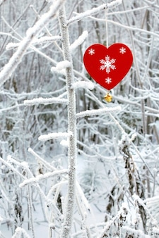 午後に木製の赤いおもちゃの心と森の霜で木の枝