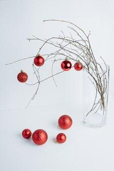 Ветви деревьев в вазе, украшенные красными орнаментами новогодняя композиция белый фон вертикаль