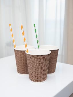 白いテーブルの上のチューブを飲むとコーヒーツーゴーのテクスチャグラス
