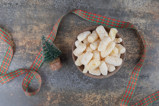 A tree figurine and festive ribbon next to a bowl of corn snacks on marble surface