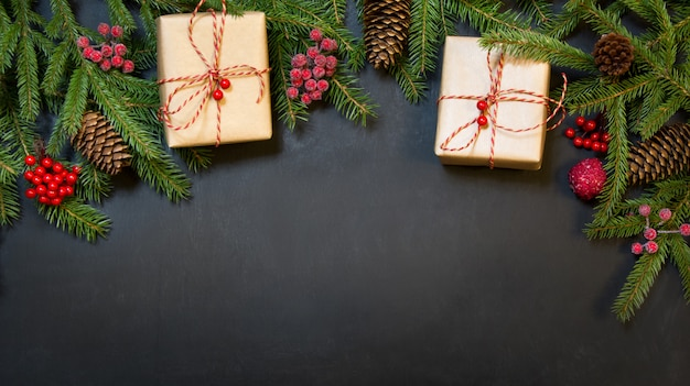 Tree, gifts, holly berries and decoration on a black chackboard.
