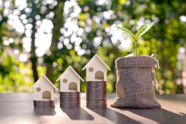 お金の概念のお金のコインの山の上のお金のバッグと家のモデルで成長している木。住宅ローン