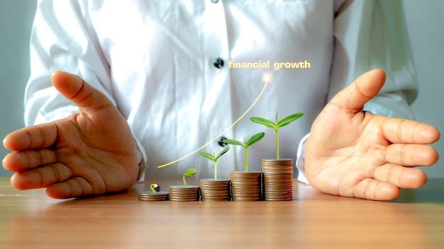 돈 더미에서 자라는 나무와 성장하는 그래프, 재정적 성장 아이디어, 비즈니스 투자로 인한 이익 극대화.