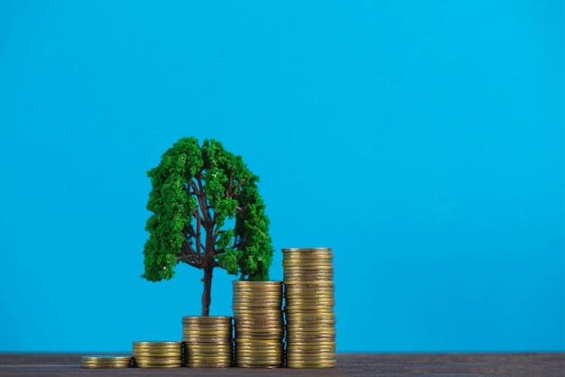 Tree growing on pile of golden coins,
