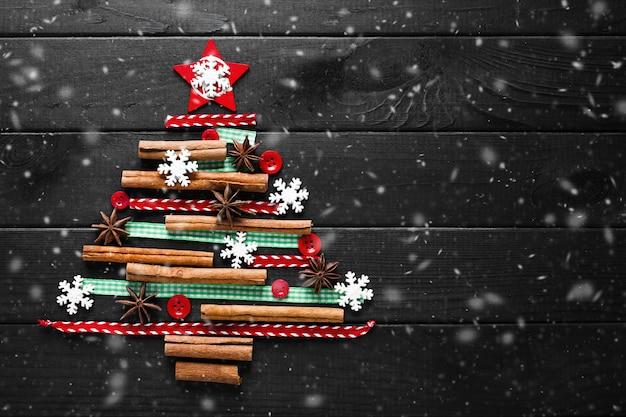 木製の暗い背景の新年カードにクリスマスの装飾で作られた木