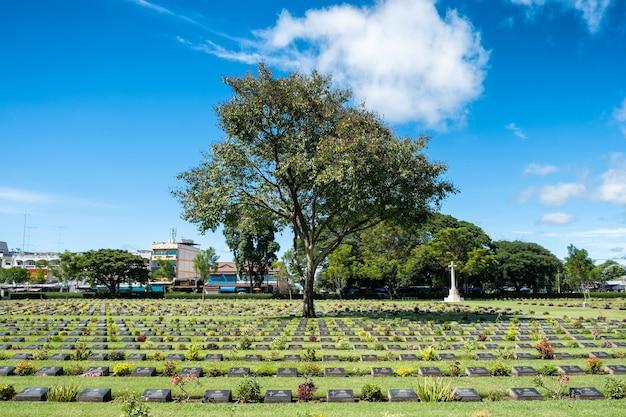 タイ、カンチャナブリでの第二次世界大戦の墓地の墓石キリスト教のvitmicsの木