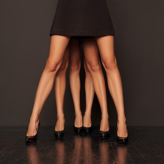 Tree pairs of female legs standing one by one