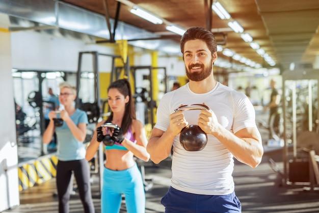 Три спортивных людей тренируются в тренажерном зале. стоять в строю и держать гири.