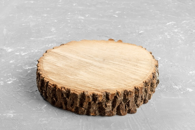 Tree stump round cut with annual rings on gray background from top view