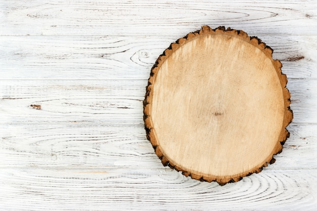 Tree stump round cut with annual rings on wooden background. top view with copy space