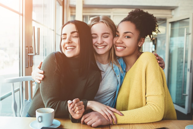 Три молодые женщины сидят вместе в маленьком кафе с большими окнами и обнимаются друг с другом.