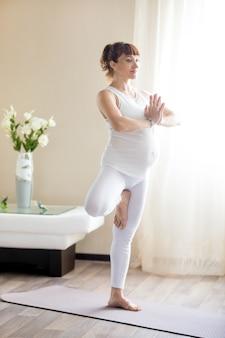 Беременная женщина делает tree йога позирует дома