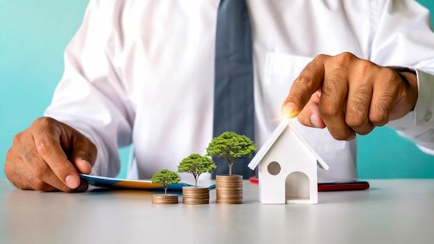 나무는 동전 더미에서 자라고 투자자들의 손은 모형 주택, 대출, 금융, 모기지, 주거용 부동산에 대한 개념을 가리키고 있습니다.