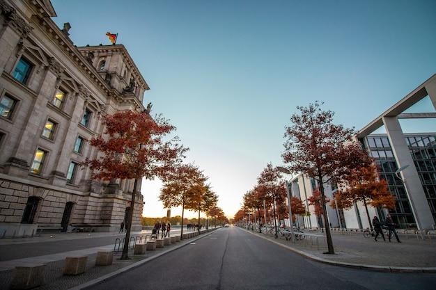 Деревья на улице и здание парламента германии слева.
