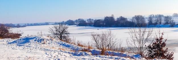 晴れた日には氷と雪の川に覆われた土手の木々