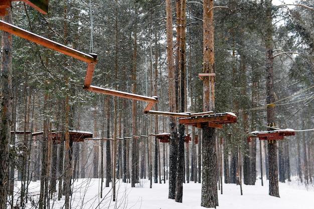 雪に覆われた冬の森にある木のてっぺんアドベンチャーパーク