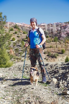 Trekker and his dog standing in the mountains