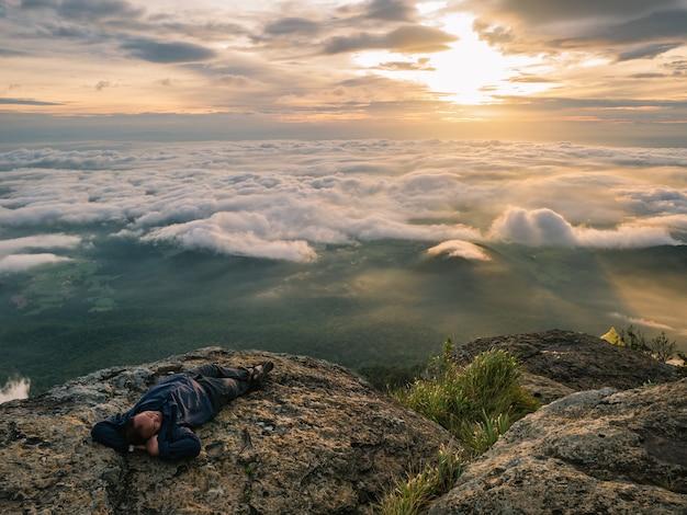 Trekker ложитесь на скале с красивым восходом солнца и морем тумана утром на горе кхао луанг в национальном парке рамкхамхаенг, провинция сукхотай, таиланд